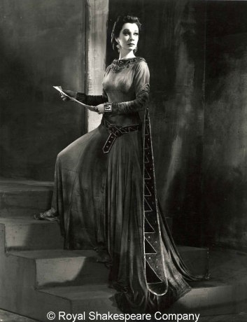 A classic black and white photo of a well dressed Lady Macbeth, holding a letter and looking over her shoulder, foot on a step.