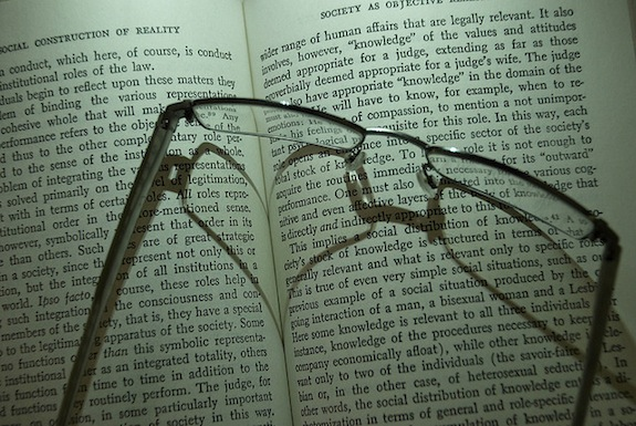 Glasses resting atop an open copy of The Social Construction of Reality