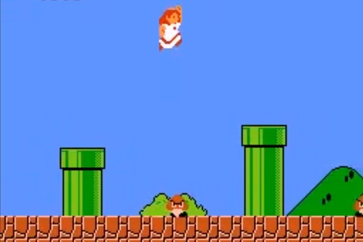16 bit video game screen showing Princess Peach wearing a white dress with red trim jumping between two green pipes against a clear blue sky with a goomba running around on the ground below.